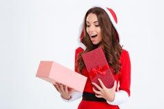 Förvånad kvinnlig i den Santa Claus dräkten som ser den närvarande asken för insida Royaltyfri Bild