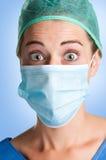 Förvånad kvinnlig kirurg med framsidamaskeringen royaltyfri foto