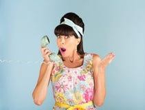 Förvånad linje telefon för kvinnainnehavland Royaltyfria Foton