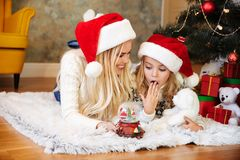 Förvånad liten flicka som får snöbollleksaken från hennes moderwhil arkivfoton