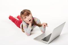 Förvånad liten flicka som ligger på magen på golvet med bärbara datorn Arkivfoto