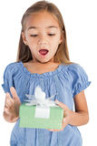 Förvånad liten flicka som rymmer en slågen in gåva Royaltyfri Foto