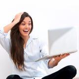 förvånad look för flickaholdingbärbar dator Arkivbild