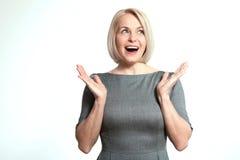 Förvånad lycklig kvinna som från sidan ser i spänning Över vitbakgrund Royaltyfri Foto