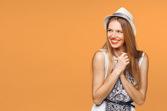 Förvånad lycklig ung kvinna som från sidan ser i spänning Isolerat över orange bakgrund arkivbild