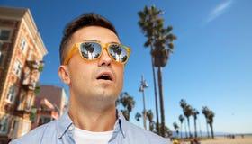 Förvånad man i solglasögon över den venice stranden royaltyfria foton
