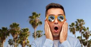 Förvånad man i solglasögon över palmträd royaltyfri fotografi