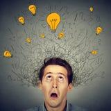 Förvånad man med många ljusa kulor för idéer ovanför huvudet som ser upp Arkivbild