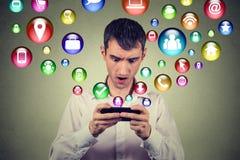 Förvånad man som använder för massmediaapplikation för smartphone som sociala symboler för symboler flyger ut ur skärmen Arkivbilder