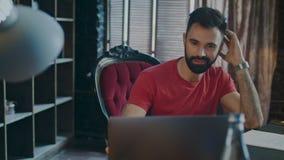 Förvånad man som ler, medan genom att använda bärbar datordatoren Affärsman som använder anteckningsboken arkivfilmer