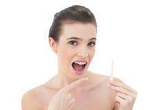 Förvånad naturlig brun haired modell som pekar en termometer med hennes finger Royaltyfri Foto