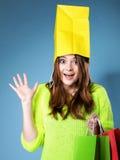 Förvånad påse för flickapappersshopping på huvudet. Försäljningar. Arkivbilder