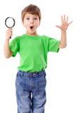 Förvånad pojke med förstoringsglaset Royaltyfria Bilder