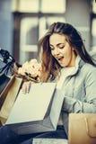 Förvånad shoppa kvinna som kontrollerar hennes påsar och le royaltyfri bild