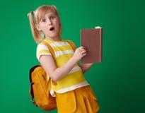 Förvånad skolaflicka med den öppna boken på grön bakgrund Arkivfoton