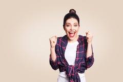 Förvånad stående av den extatiska unga kvinnan för lycklig vinnare med tillfällig stil som har chockad blick som utropar royaltyfri fotografi
