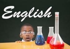Förvånad studentpojke på tabellen mot den gröna svart tavla med engelsk text Royaltyfri Fotografi