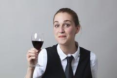 Förvånad 20-talflicka som dricker rött vin på partiet för att fira framgång på den passande sommelieren Royaltyfri Foto