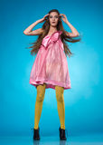 Förvånad tonårig flicka i en rosa klänning arkivbild