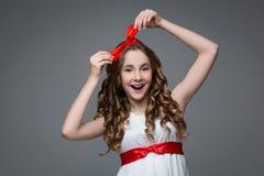 Förvånad tonårig flicka med den röda pilbågen på huvudet royaltyfri foto
