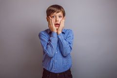 Förvånad tonåringpojke på grå bakgrund Royaltyfria Foton