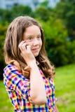 Förvånad tonårs- flicka i tillfällig kläder som talar vid mobiltelefonen Arkivfoto