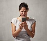 Förvånad uncontented kvinna med smartphonen arkivbild