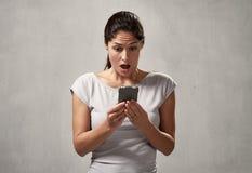Förvånad uncontented kvinna med smartphonen arkivfoton