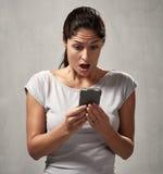 Förvånad uncontented kvinna med smartphonen royaltyfri bild