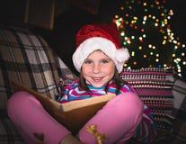 Förvånad ung flicka i en julhatt med en bok Arkivfoto