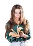 Förvånad ung flicka och att bläddra till och med sidorna av boken för att isolera Läser shock Arkivfoto