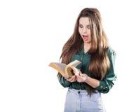 Förvånad ung flicka och att bläddra till och med sidorna av boken till Arkivfoton
