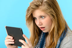 Förvånad ung flicka som rymmer den digitala minnestavlan Royaltyfri Fotografi