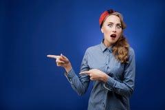 Förvånad ung kvinna med öppna kanter som visar av fingrar på ditt Arkivbild