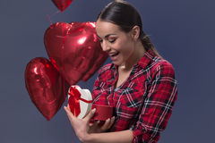 Förvånad ung kvinna med en gåva för dag för valentin` s Royaltyfri Fotografi