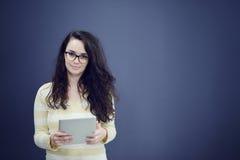 Förvånad ung kvinna som använder rymma en digital minnestavla arkivbild