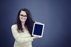 Förvånad ung kvinna som använder rymma en digital minnestavla royaltyfri bild