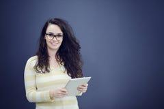 Förvånad ung kvinna som använder rymma en digital minnestavla royaltyfri fotografi