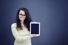 Förvånad ung kvinna som använder rymma en digital minnestavla arkivfoton