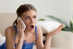 Förvånad ung kvinna som talar på mobiltelefonen royaltyfria bilder