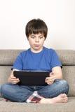 Förvånad ung pojke och en digital minnestavla Royaltyfria Foton