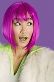 Förvånad ung skraj kvinna i den rosa peruken som från sidan ser över purpurfärgad bakgrund Arkivbilder