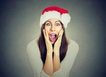 Förvånad upphetsad lycklig kvinna som bär den röda Santa Claus hatten som ser chockad Arkivbild