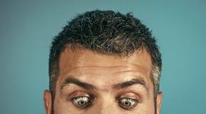 Förvånade ögon Ögon av mannen med den förvånade framsidan på blå bakgrund royaltyfri fotografi