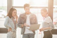 Förvånade affärskollegor man och kvinnor med bärbara datorn arkivfoton