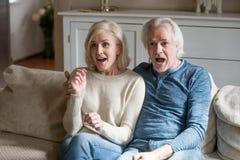 Förvånade häpna höga par som håller ögonen på ny verklighetshow på tele arkivbild