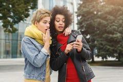 Förvånade kvinnliga vänner lyssnar till musik utomhus arkivbild