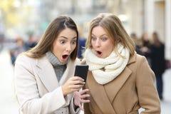 Förvånade kvinnor som läser telefoninnehållet i vinter i gatan royaltyfria bilder