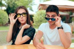 Förvånade par som bär matcha moderiktig modesolglasögon royaltyfri foto