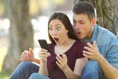 Förvånade par som finner det fantastiska innehållet på linje arkivfoto